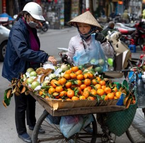 FCE Speaking - Two people buying fruit from a street vendor somewhere in Asia