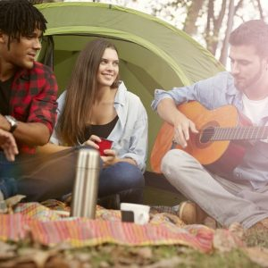 FCE Speaking Part 2 Card - a group of people camping, drinking tea and listening to live guitar music