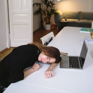 a woman is sleeping on her desk in front of a laptop