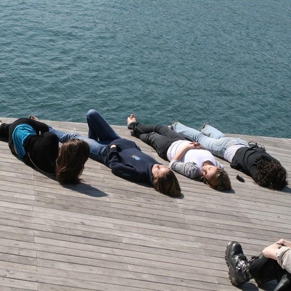 four women relaxing on a pier